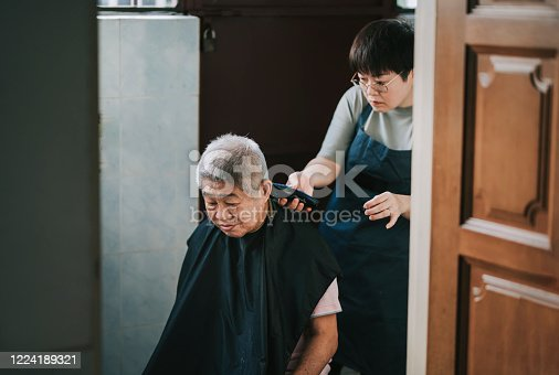 an asian chinese mid adult woman is cutting and trimming hair for her father in the kitchen due to travel ban