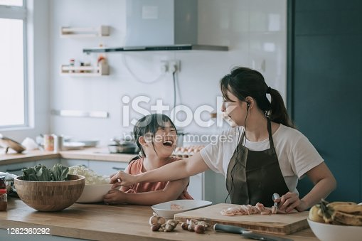 istock an asian chinese mother cooking preparing food at kitchen counter  with her daughter 1262360292