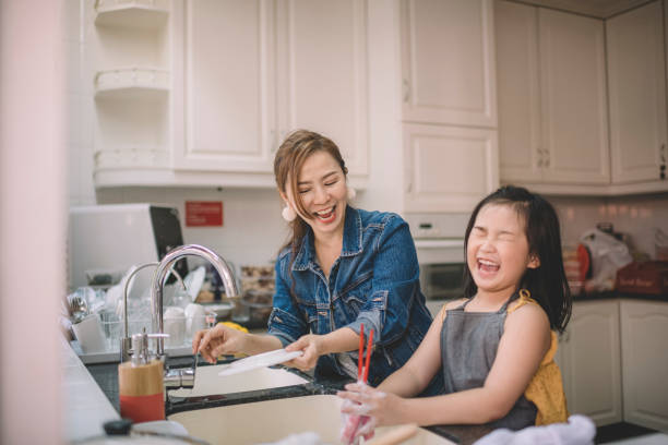 an asian chinese mother washing dishes with her daughter in the kitchen and having fun time bonding stock photo