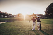 an asian chinese senior man golfer carrying his golf club on his shoulder and looking at the view in golf course