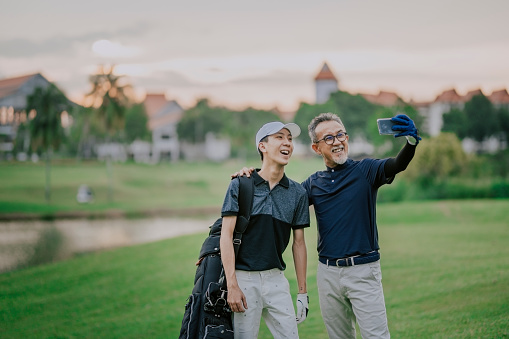 an asian chinese senior man golfer having selfie with his son after winning the golf game with toothy smile