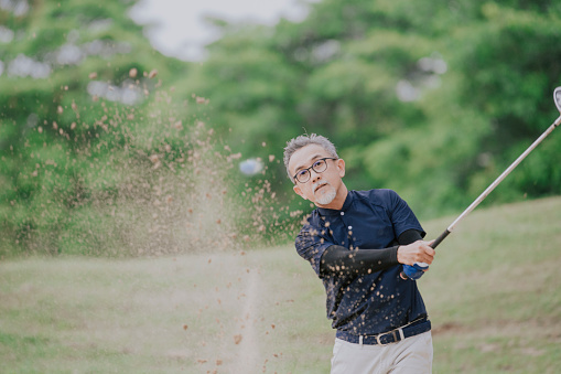 an asian chinese senior man golfer hitting his golf ball in a sand trap with his iron club