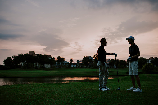 an asian chinese senior man golfer talking to his son after the game in golf course