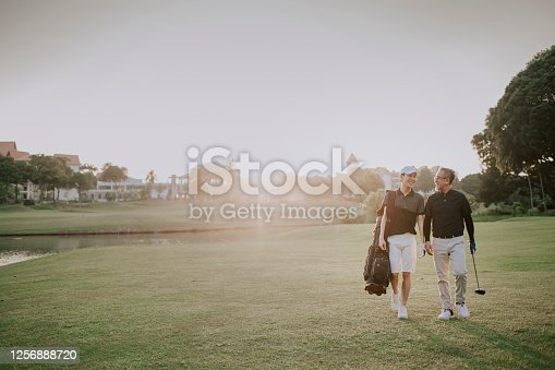 an asian chinese senior man golfer walking and talking to his son who carrying golf bag at the end of the game happily in melaka golf course