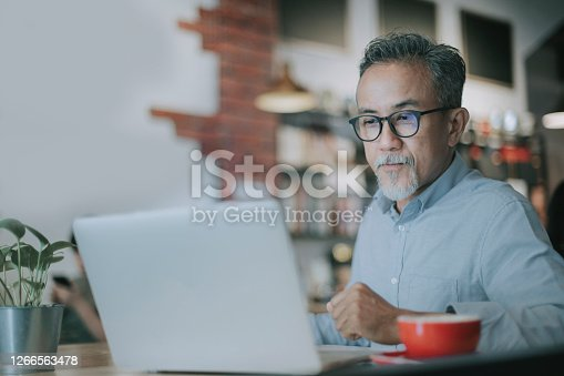 an asian chinese senior man having discussion with his colleague via online virtual meeting