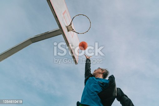 an asian chinese senior man practicing basket ball game in the basket ball court in the morning