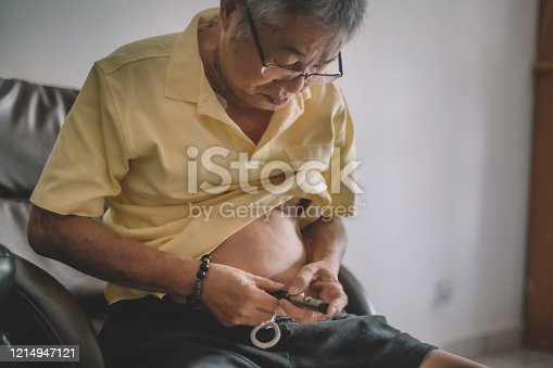 an asian chinese senior man putting a syringe insulin injection on his stomach abdomen on daily basis
