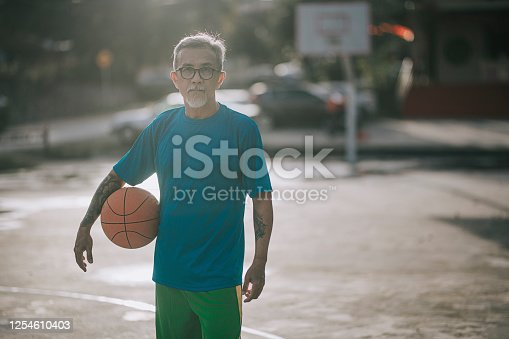 an asian chinese senior man resting after playing basket ball game in the basket ball court in the morning with his daughter