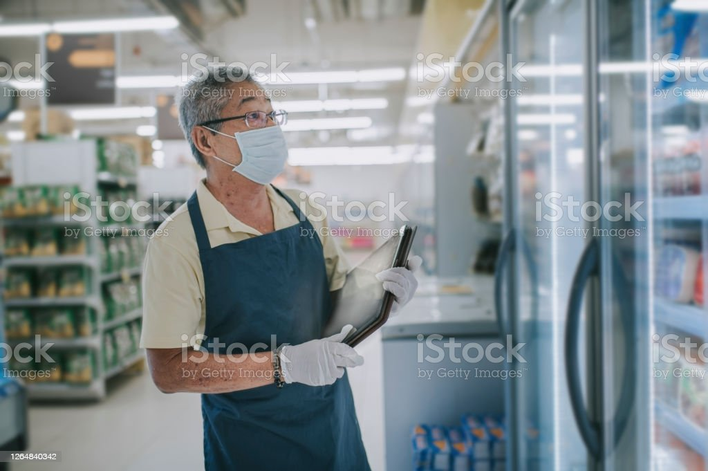 an asian chinese senior man supermarket shopkeeper retail assistant with face mask an asian chinese supermarket shopkeeper retail assistant Active Seniors Stock Photo