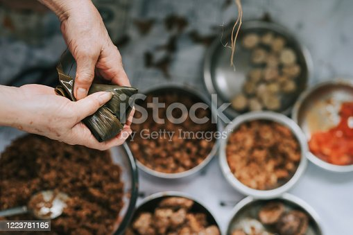an asian chinese senior woman preparing zongzi chinese dumpling in her kitchen putting ingredient and wrapping it