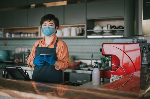 フェイスマスクと保護手袋を持つアジアの中国の中小企業の所有者は、カメラを見て微笑むキッチンカウンターで彼女の顧客にデザートを渡します - business malaysia ストックフォトと画像
