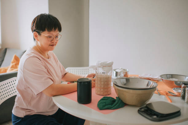 an asian chinese stay home mother preparing dough while using virtual assistant smart speaker for recipe and guidance - baking bread at home imagens e fotografias de stock