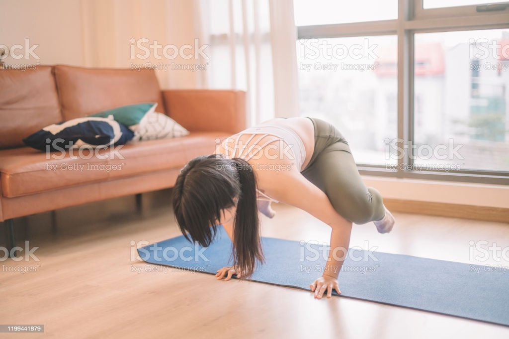 An Asian Chinese Teenage Girl Doing Yoga Pose Firefly Tittibhasana In Her Living Room With Yoga Mat Morning Before She Goes To College Stock Photo Download Image Now Istock