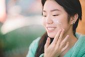 an asian chinese teenager girl applying moisturiser facial cream on hand and face