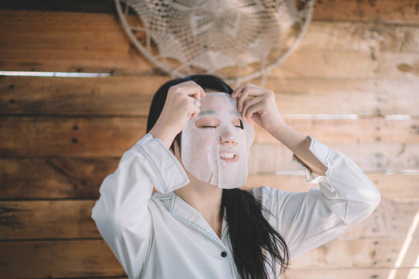 an asian chinese teenager girl putting a facial sheet mask on her face stock photo