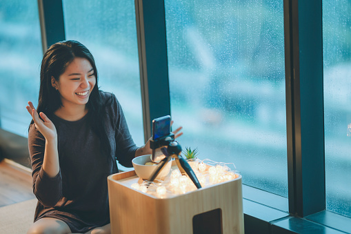 an asian chinese teenager girl vlogging in her room eating apple using her smart phone during raining day smiling