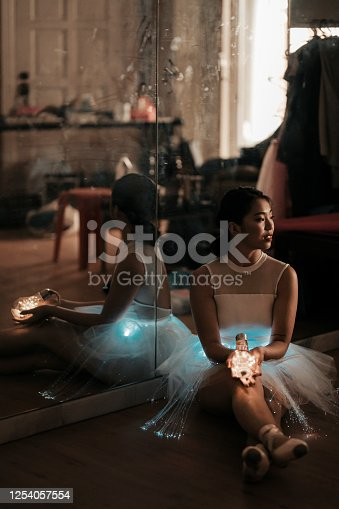 an asian chinese teenager holiding a light bulb with LEd light on hand in the living room on dark environment