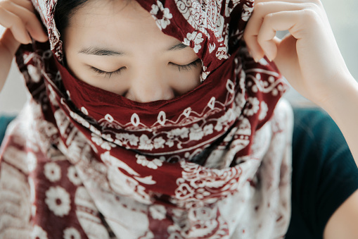 An asian chinese woman portrait headshot with her headscarf covering mouth