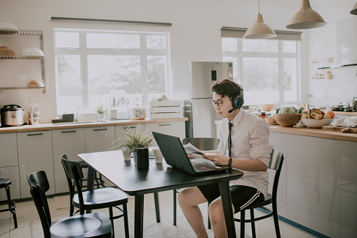 An asian chinese young adult man with tie, long sleeve shirt and short pant sitting using laptop in his dining room for video conference with his business partner and colleague virtual business meeting