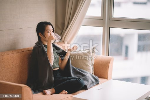 an asian chinese young female sitting on sofa with sickness cover with blanket taking medicine