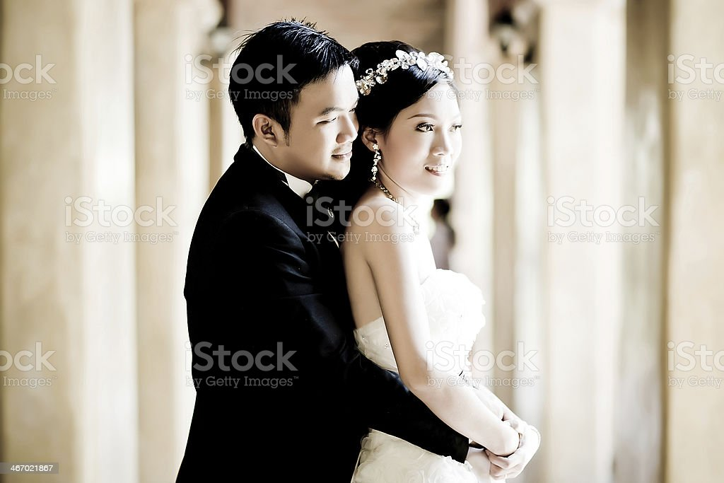 An Asian couple in wedding attire smile and embrace stock photo