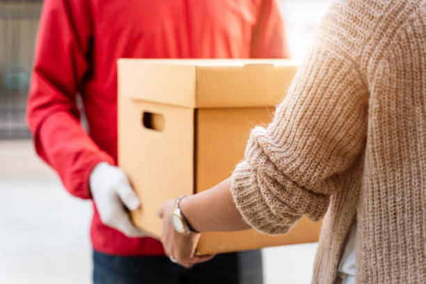 An Asian delivery man in a red uniform handing the parcel to a female customer in front of the house. A postman and express delivery service deliver a parcel during the covid19 pandemic. stock photo