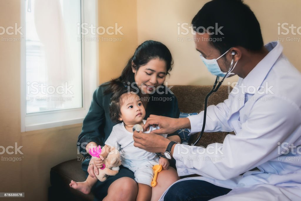 Ein asiatische Arzt ist Überprüfung der Symptome für ein krankes Mädchen und ihre Mutter mit ihr. – Foto