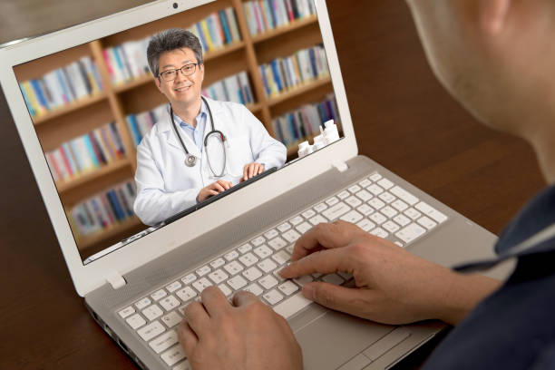 an asian doctor who is remotely consulting with a patient. telehealth concept - telecomando background foto e immagini stock