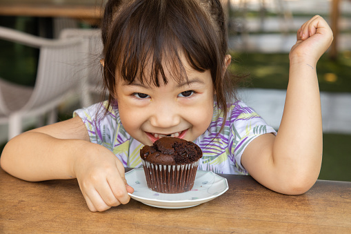 An Asian girl, about 3 years old, has a cute face, is eating a cake as a delicious snack, and it makes the people who saw it smile happily.