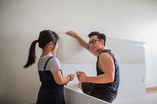 An Asian girl is helping father installing furniture. She is holding a tools and ready for her father.