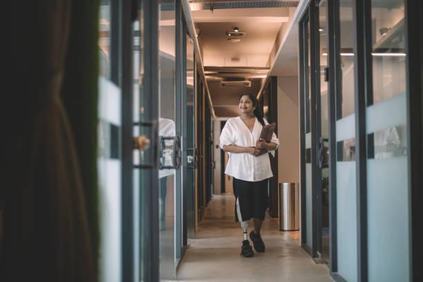 une travailleuse indienne asiatique handicapée de collier blanc avec le membre prosthétique retenant sa tablette numérique et marchant au sourire de couloir de bureau - business malaysia photos et images de collection