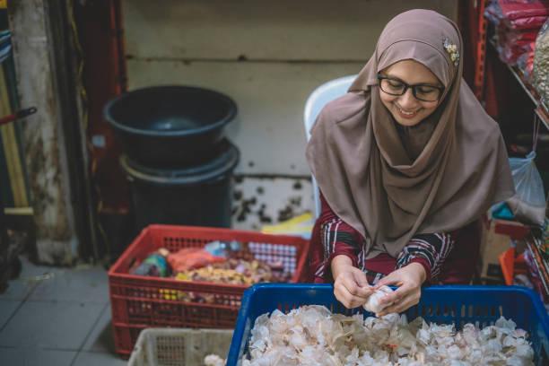 un propriétaire de magasin féminin malay asiatique avec le hijab épluchant outre de la peau d'oignon à son magasin dans le marché - business malaysia photos et images de collection