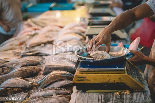 an asian malay fish seller weighing the fish which selected by his customer for the price