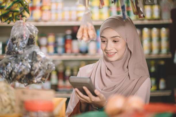an asian malay groceries shop female owner with hijab calculating the price of the item for her customer an asian malay groceries shop female owner with hijab calculating the price of the item for her customer business Malaysia stock pictures, royalty-free photos & images