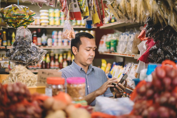 an asian malay mid adult calculating the cost for his customer's selected items an asian malay mid adult calculating the cost for his customer's selected items grocer stock pictures, royalty-free photos & images