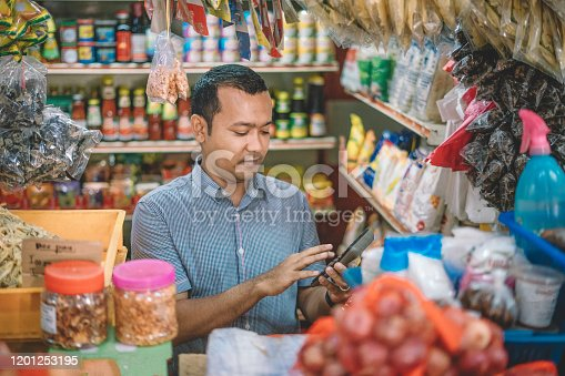 An asian malay mid adult calculating the cost for his customer's selected items