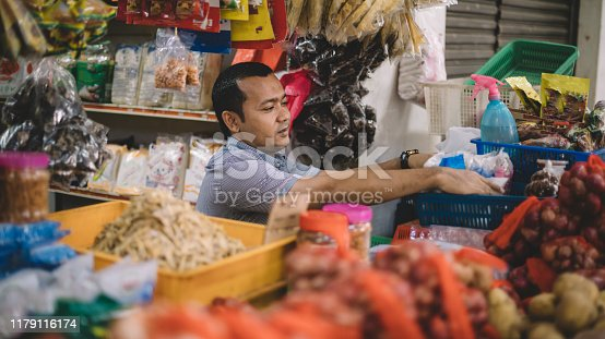 an asian malay mid adult opening spice store and getting ready for the day