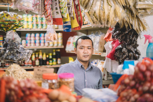an asian malay mid adult opening spice store and getting ready for the day looking at camera stock photo