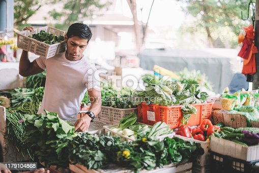 an asian malay vegetable owner arranging vegetables at his stall getting ready for the day