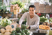 an asian malay vegetable retail owner arranging his vegetables getting ready for the business looking at camera