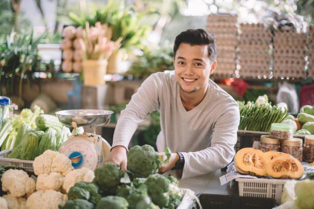 un propriétaire asiatique malay légumes au détail organiser ses légumes se préparer pour l'entreprise en regardant la caméra - business malaysia photos et images de collection