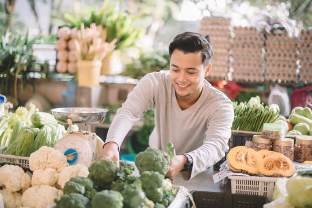 an asian malay vegetable retail owner arranging his vegetables getting ready for the business stock photo