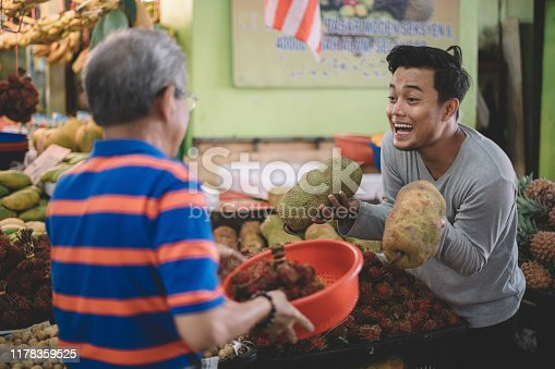 an asian male fruit stall owner selling jack-fruit to a chinese senior man at his stall