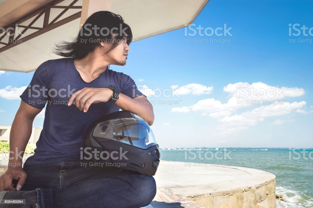 An Asian man sitting under roof next to the sea with his helmet while...