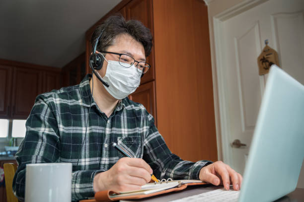 An Asian man who is self-isolated and working from home because of a massive pandemic. stock photo