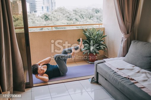 925799546 istock photo an asian mid adult woman workout yoga at home balcony during the restricted movement order in malaysia 1217730533