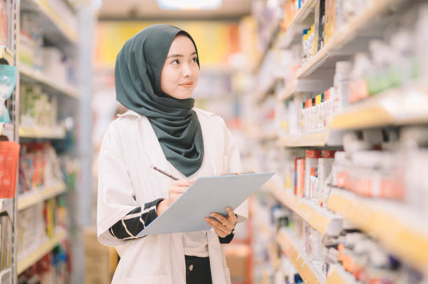 an asian modern muslim pharmacist lady with hijab recording the stock level of the medicine in a pharmacy store stock photo