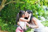Asian child kissing her mother. Asian family having fun outdoor, biking outdoor.