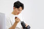 An Asian photographer is cleaning the camera and lens with a blower.