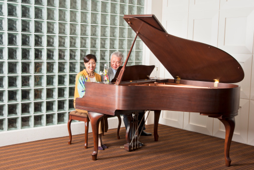 An Asian senior couple playing the grand piano